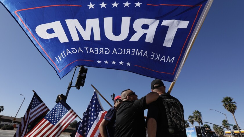 A small group of anti-Sharia demonstrators wave Trump banners at the site of the 2015 San Bernardino