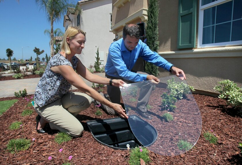 In the front yard of a model home at KB Home's Sea Cliff development ,Heather McPherson and Tom Wood, of Nexus eWater, remove the cover of the home's gray water tank. The water will be treated by the home's gray water recycling system. Nexus Water makes the home's gray water system.