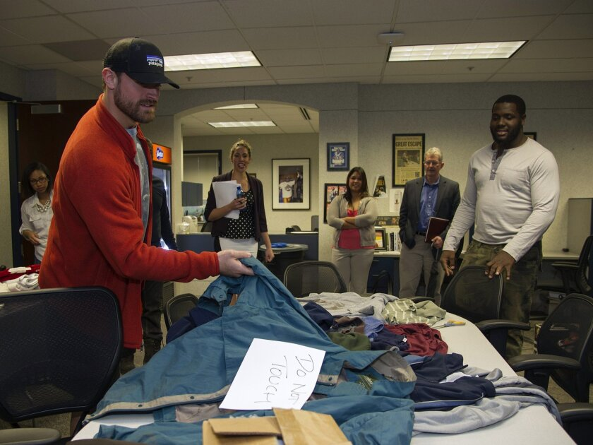 St. Louis Rams defensive linemen Chris Long (left) and William Hayes (right) pick out clothes to wear as they prepare to go homeless for a day in St. Louis.