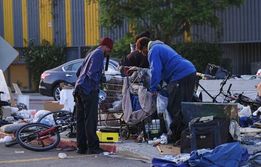 Homeless men sort through their belongings on a traffic island near downtown Los Angeles last week.