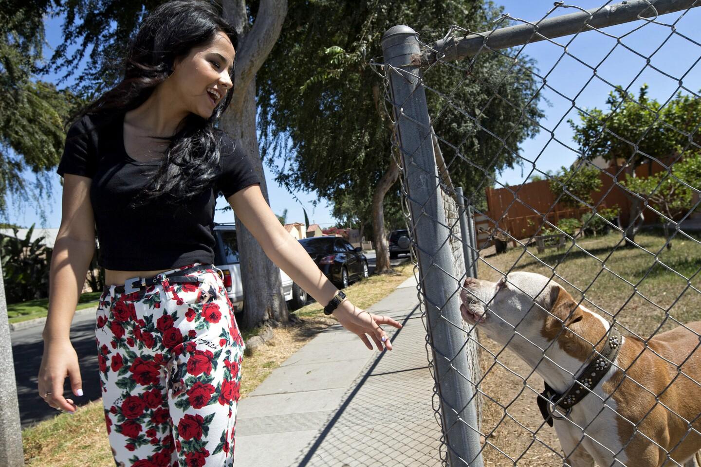 Rebbeca Marie Gomez, 16, a.k.a. Becky G, is greeted by a neighborhood dog as she walks along Oak Street in Inglewood.