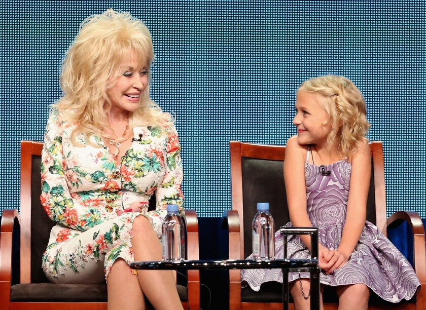 Executive producer Dolly Parton and actress Alyvia Lind speak onstage during NBC's 'Dolly Parton's Coat of Many Colors' panel discussion at the NBCUniversal portion of the TCA summer press tour at the Beverly Hilton.