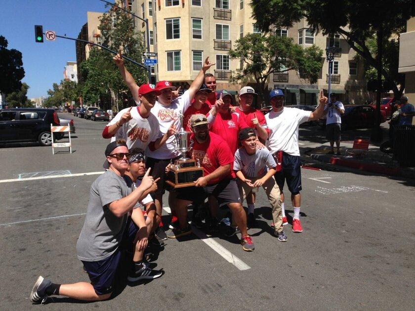 The San Diego Street Rookies gather around their stickball tournament trophy on India Street.