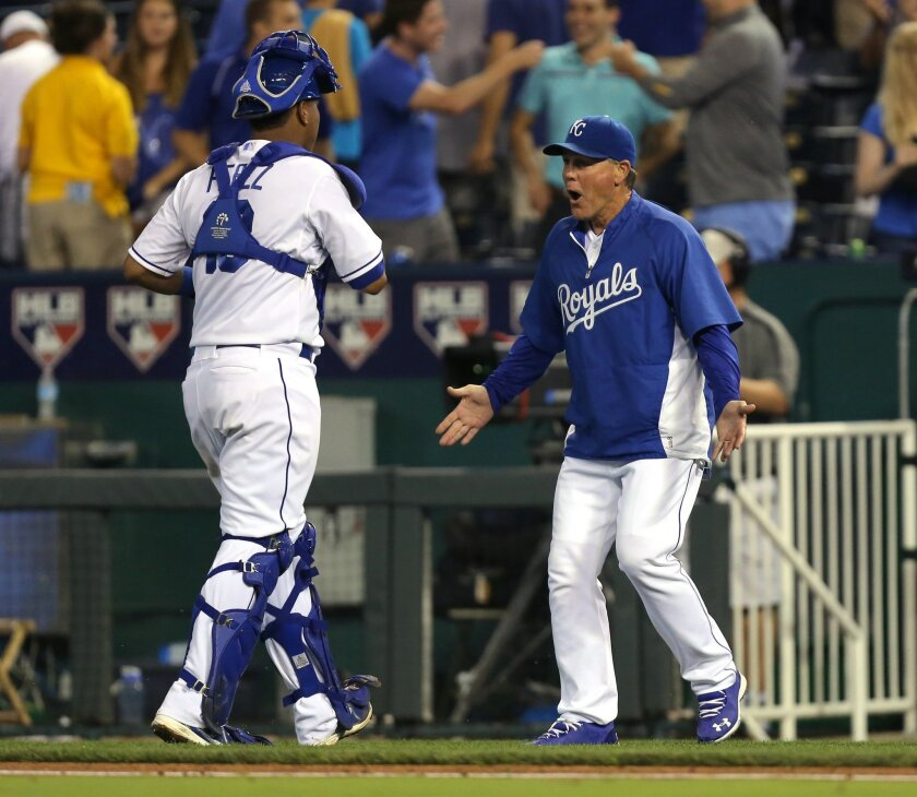 Kansas City Royals manager Ned Yost, right, and catcher Salvador Perez celebrate a 3-2 win over the Minnesota Twins after the baseball game Wednesday, July 30, 2014, in Kansas City, Mo.  (AP Photo/Ed Zurga)