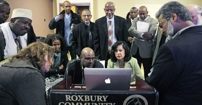 In this March 2015 photo, Muslim, Christian, minority and government leaders watch a video as part of a federal pilot program called Countering Violent Extremism, at Roxbury Community College in Boston.