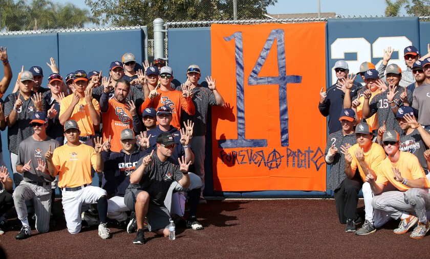 Orange Coast College players and coaches gather around a banner at the school's baseball field Monday to honor head coach John Altobelli, who died with his wife, Keri, and daughter Alyssa in Sunday's helicopter crash in Calabasas that also claimed the lives of Lakers great Kobe Bryant and five others.