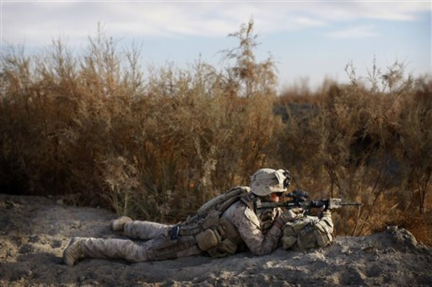 An unidentified United States Marines from the 2nd MEB, 4th Light Armored Reconnaissance Battalion takes a position, during a patrol near Khan Nashin in the volatile province of Helmand, southern Afghanistan, Sunday, Dec. 6, 2009. (AP Photo/Kevin Frayer)