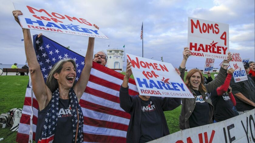 Supporters of Harley Rouda shout for their candidate during a get out the vote rally at Main Beach in Laguna Beach, Calif. on Nov. 6.