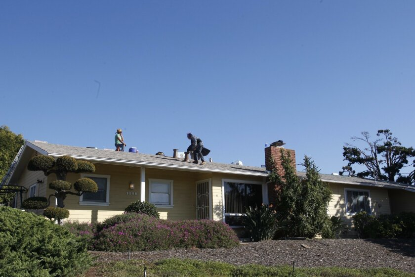 CARLSBAD, CA-Nov. 13, 2015:RC Roofing Company roofers re-roofed a house in Carlsbad on Friday, November 13, 2015. Median home prices across San Diego County rose 2.5 percent to $468,100 in November. JOHN GIBBINS / San Diego Union-Tribune)