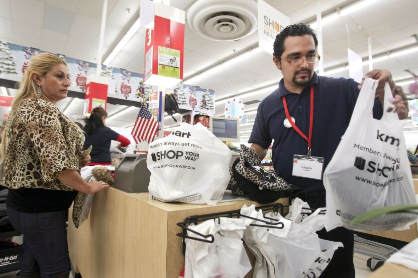 U-T File: In this photo taken Nov. 28, 2013, Kmart cashier Eduardo Pinales puts purchased items in bags for a customer at the Kmart on University Avenue in San Diego.