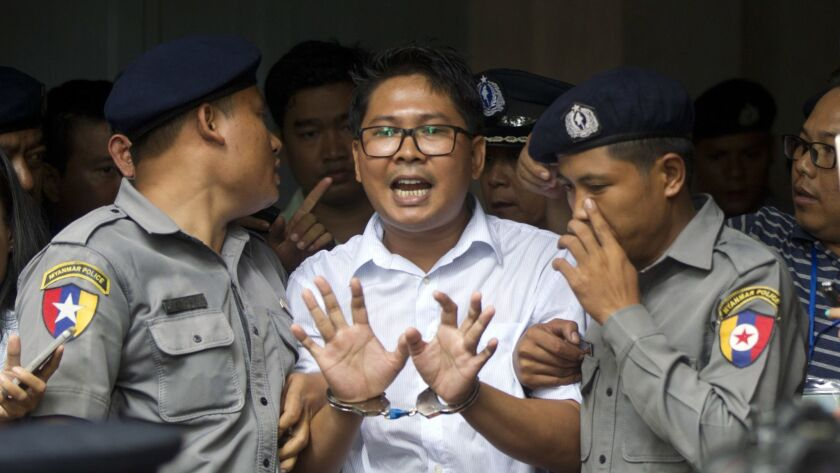Reuters journalist Wa Lone talks to reporters as he is escorted by police from a court in Yangon, Myanmar, on Sept. 3, 2018.