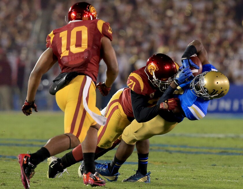 UCLA receiver Mossi Johnson holds on to a pass for a first down despite receiving a big hit from USC linebacker Su'a Cravens during the second quarter Saturday night at the Rose Bowl.