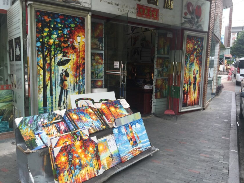 Paintings are displayed on a street in China's Dafen Oil Painting Village.