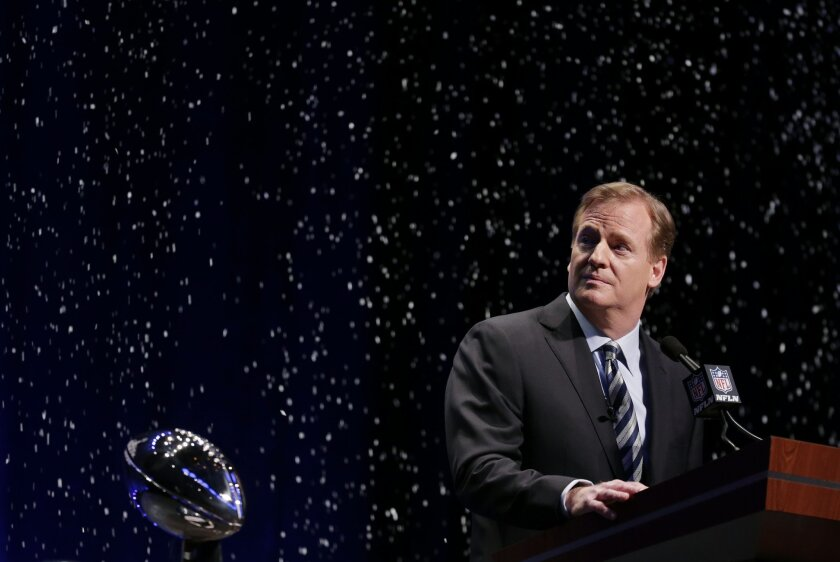 NFL comissioner Roger Goodell looks at artificial snow falls on stage as he speaks at a news conference Friday, Jan. 31, 2014, in New York. The Seattle Seahawks are scheduled to play the Denver Broncos in the NFL Super Bowl XLVIII football game on Sunday, Feb. 2, at MetLife Stadium in East Rutherfo