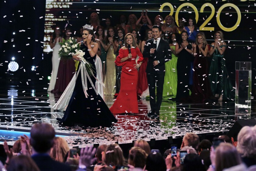 FILE - In this Dec. 19, 2019, file photo, Camille Schrier, of Virginia, left, reacts after winning the Miss America competition at the Mohegan Sun casino in Uncasville, Conn. The 100th Miss America will be crowned before a live audience at the Mohegan Sun casino in Connecticut following a year of virtual appearances and postponed competitions due to the pandemic, organizers announced Thursday, April 8, 2021. (AP Photo/Charles Krupa, File)