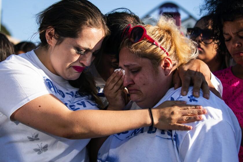 Katiuska Pimentel, left, aunt of Gilroy shooting victim Keyla Salazar, hugs Keyla's parents Juan Salazar and Lorena de Salazar before a San Jose vigil.