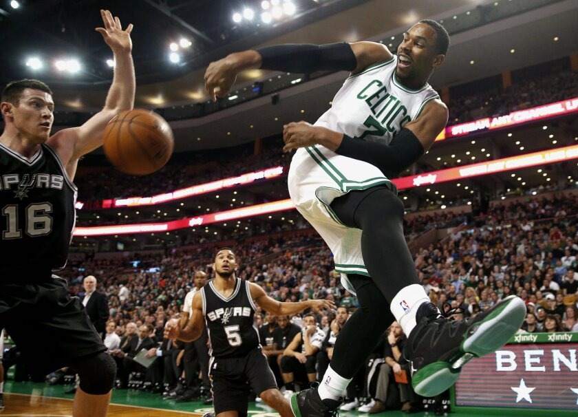 Boston Celtics' Jared Sullinger keeps the ball inbounds and throws it off of San Antonio Spurs' Aron Baynes during the first quarter of an NBA basketball game in Boston Sunday, Nov. 30, 2014. (AP Photo/Winslow Townson)