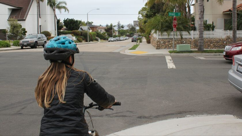 La Jolla 11-year-old resident Charlotte Norton eyes the next sidewalk where she will ride her bike b