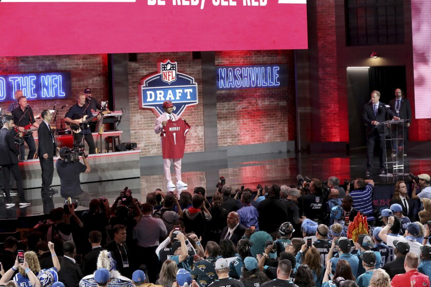 Kyler Murray poses with a jersey after being selected by the Arizona Cardinals with the first pick d