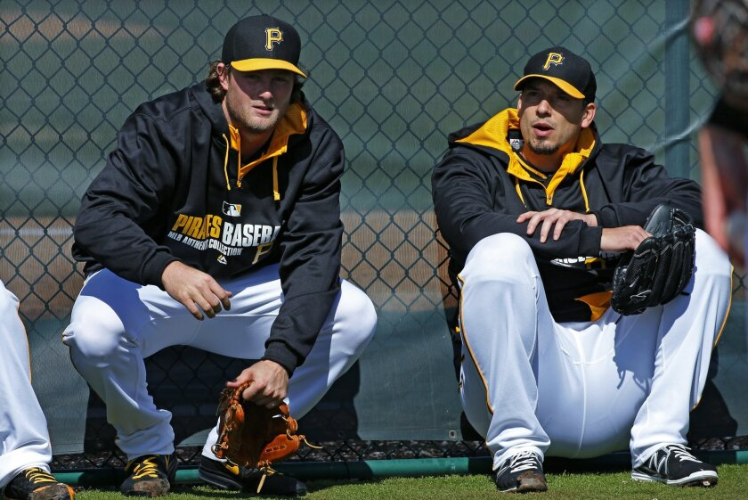 Pittsburgh Pirates pitchers Gerrit Cole, left, and Charlie Morton take a break after throwing a bullpen session on the baseball team's first day of spring training for pitchers and catchers, in Bradenton, Fla., Thursday, Feb. 13, 2014. (AP Photo/Gene J. Puskar)
