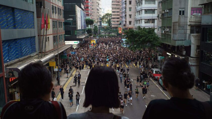 Bystanders watch from a footbridge June 16 as protesters march towards the government headquarters in Hong Kong Thursday.