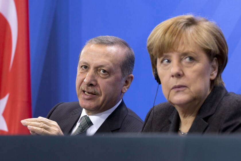In this Feb. 4 file picture, German Chancellor Angela Merkel listens to Turkish President Recep Tayyip Erdogan during a joint news conference after a meeting in Berlin.