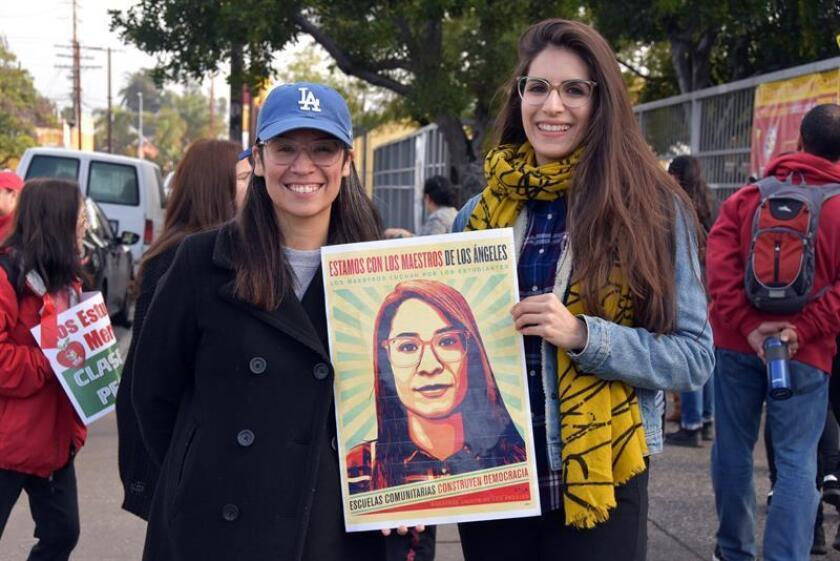 Las maestras de la escuela secundaria Theodore Roosevelt, de Historia, Roxana Dueñas (i), y de Matemáticas, Aleida Pérez (d), posan con el afiche de la huelga del Sindicato de Maestros de Los Ángeles (UTLA) con la cara de Dueñas, en las afueras de la escuela este viernes en Los Ángeles, California (EE.UU). EFE