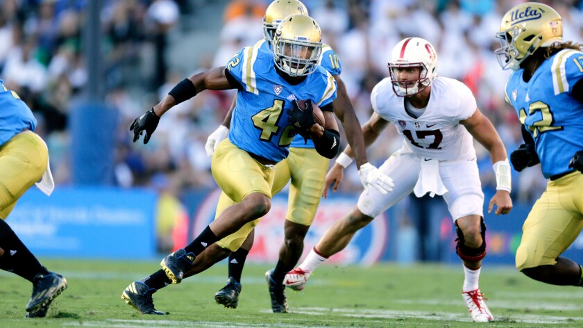 Kenny Young  runs with the ball after picking off a pass by Stanford quarterback Ryan Burns on Sept. 24.