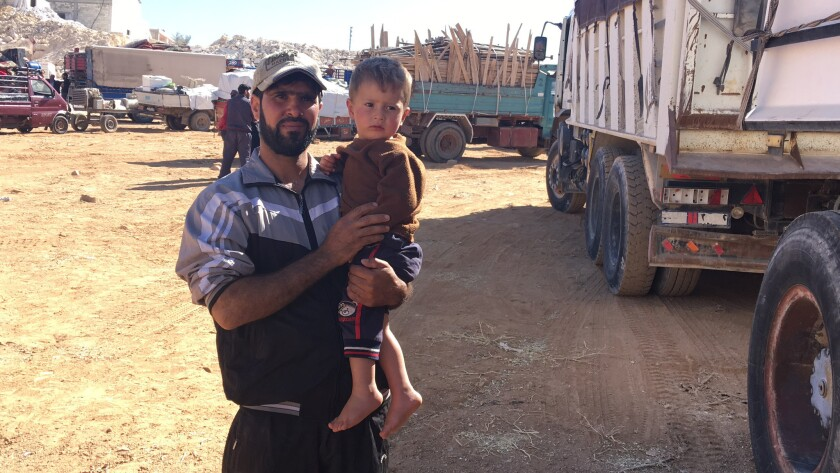 Syrian refugee Mahmoud Refai holds up his 1-year-old son, Yazan, as they wait to bid farewell to hi