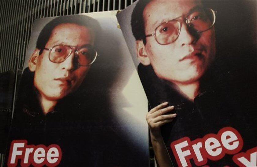 """FILE - In this Oct. 23, 2009 file photo, pro-democracy activists hold pictures of Chinese dissident Liu Xiaobo, who was arrested after co-authoring a bold manifesto urging civil rights and political reform, outside the U.S. Consulate General in Hong Kong. Hong Kong police arrested five pro-democracy protesters after demonstrators scuffled with officers guarding the central Chinese government's local liaison office Friday, Oct. 1, 2010. The clash broke out when about 100 protesters marked National Day by marching to the liaison office denouncing Beijing's """"authoritarian rule"""" and demanding the release of dissident Liu, who is serving an 11-year jail term for inciting subversion. (AP Photo/Kin Cheung, File)"""