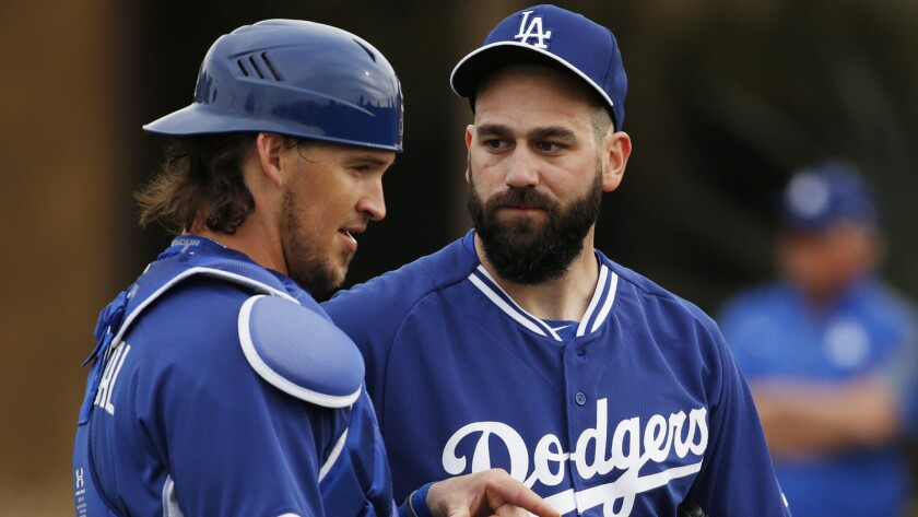 Los Angeles Dodgers' Yasmani Grandal, left, speaks with Chris Hatcher during the team's first pitchers and catchers workout on Feb. 20, 2015, in Phoenix.