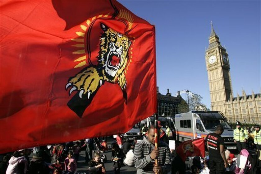 A Tamil Tiger flag is carried as protesters sit during a protest on the street outside the Houses of Parliament in London, Monday, May 11, 2009. Hundreds of pro-Tamil demonstrators blocked traffic and clashed with police in the streets around Britain's Parliament Monday after news filtered out from Sri Lanka that hundreds of their compatriots had died in intense shelling. Police said Monday evening that 36 people had been arrested and the protesters had been cleared from the roads. (AP Photo/Akira Suemori)