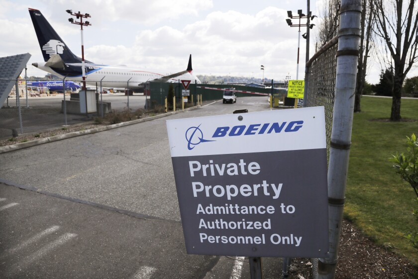 FILE - In this April 20, 2020, file photo, planes sit parked behind a sign marking Boeing property at a Boeing production plant in Renton, Wash. Relatives of people who died in one of the Boeing 737 Max crashes are renewing their push to replace top regulators who approved the plane. Several of the family members met Wednesday, May 5, 2021, with top officials of the Transportation Department. Hundreds more relatives and friends signed a letter demanding that President Joe Biden replace the head of the Federal Aviation Administration and other top FAA officials. (AP Photo/Elaine Thompson, File)