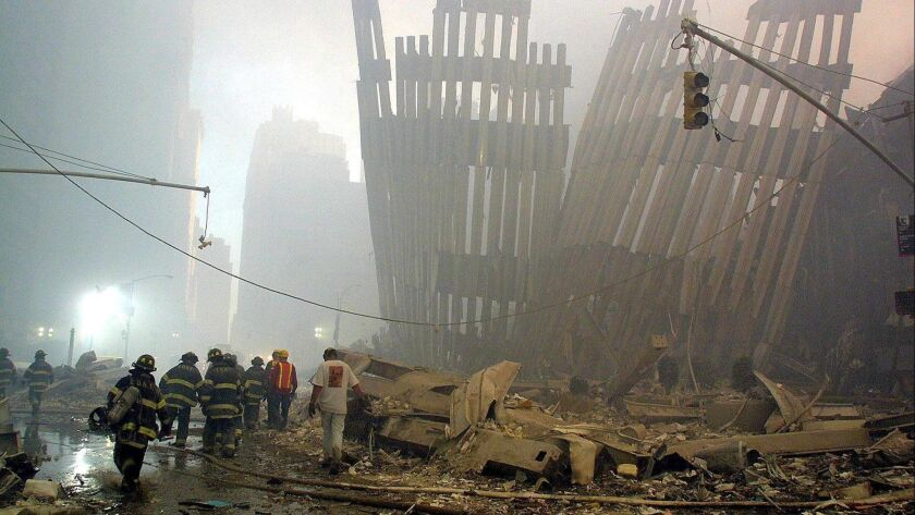 Firefighters make their way through the rubble of the World Trade Center 11 September 2001 in New Yo