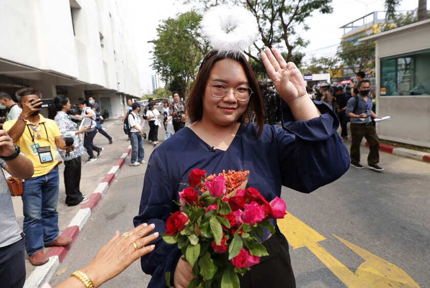 In this Monday, March 8, 2021, photo, pro-democracy activist Panusaya Sithijirawattanakul gestures with a three-fingers salute, a symbol of resistance, as she arrived at the Attorney General office in Bangkok, Thailand. Panusaya, one of the pro-democracy leaders, has been released on a THB$200,000 (USD$6,400) bail with a condition that she has to wear an electronic monitoring bracelet. (AP Photo/Sakchai Lalit)
