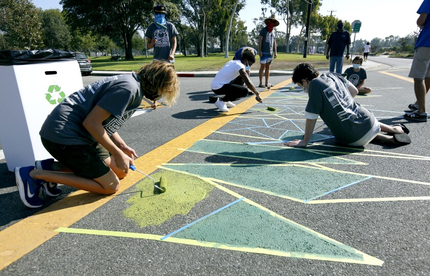 Silas Newcott, 14 of Costa Mesa, left, paints a crosswalk at Arlington Drive during Love Costa Mesa 2020 in October.