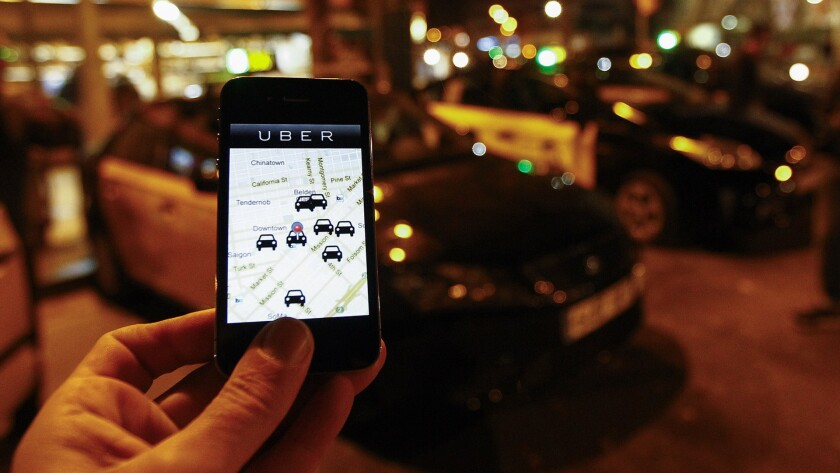 The Uber app is seen on a smartphone past cabs waiting for riders.