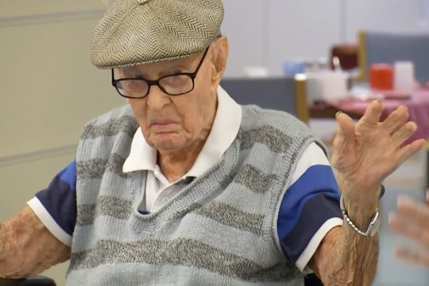 In this image made from video, Australia's Dexter Kruger gestures at a nursing home in the rural Queensland state town of Roma, Australia on May 13, 2021. Kruger, Australia's oldest-ever man, has included eating chicken brains among his secrets to living more than 111 years. The retired cattle rancher on Monday, May 17, 2021, marked 124 days since he turned 111, a day older than World War I veteran Jack Lockett was when he died in 2002. (Australian Broadcasting Corporation via AP)