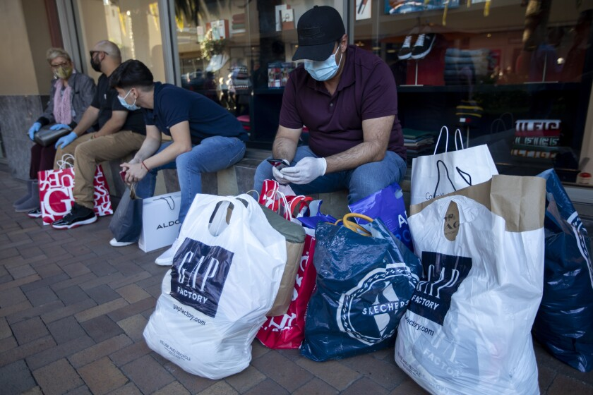 Shoppers wait with their bags at the Citadel Outlets in Commerce on Nov. 28.