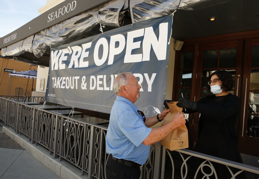 Customer picks up an order at Lure Fish House in downtown Ventura