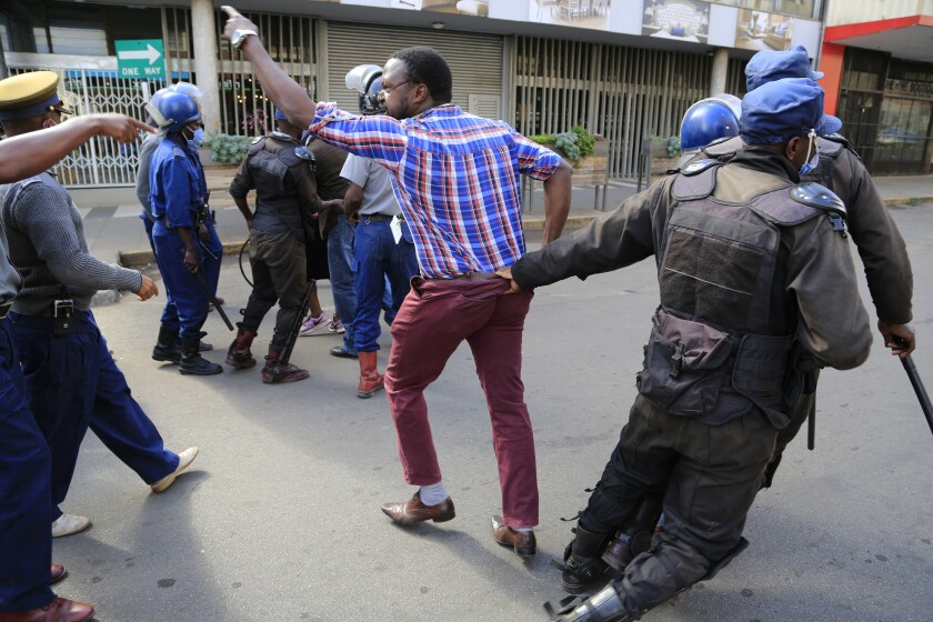 Zimbabwe police arrest opposition supporters outside their party headquarters in Harare, Friday, June, 5, 2020. Armed riot police fired teargas and arrested several opposition leaders who had gathered at the party offices after it had been forcibly occupied by a rival faction with the help of state security agents. Zimbabwes main opposition MDC party is mired in divisions after a court ruled in March this year that Nelson Chamisa, who narrowly lost to President Emmerson Mnanagawa in 2018 elections, is not the legitimate leader of the party.(AP Photo/Tsvangirayi Mukwazhi)