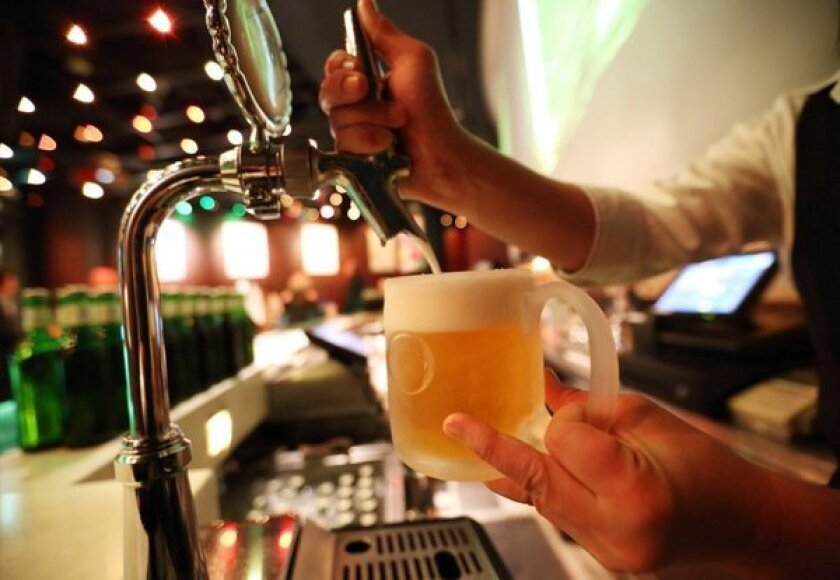 A bartender pours beer from a tap.