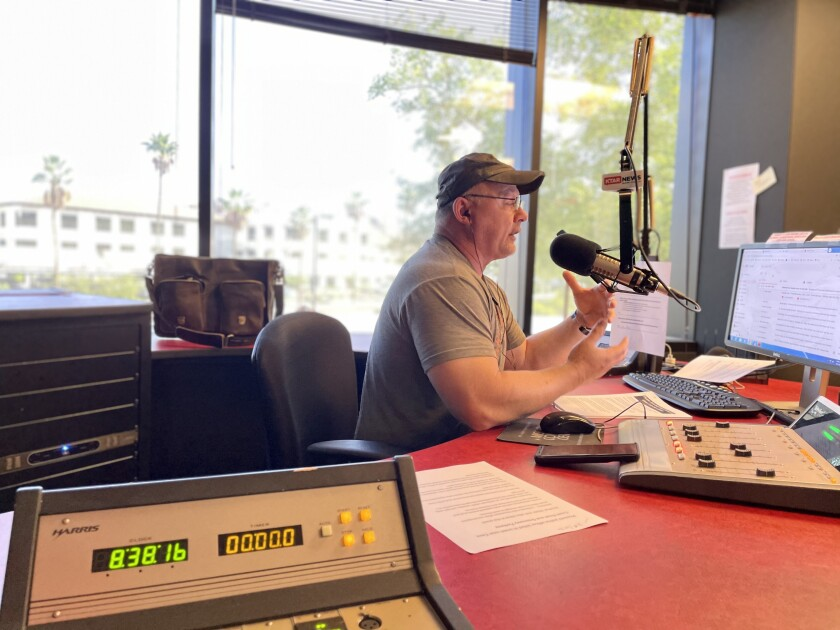 Mike Broomhead, in glasses and T-shirt, sits at his radio booth.