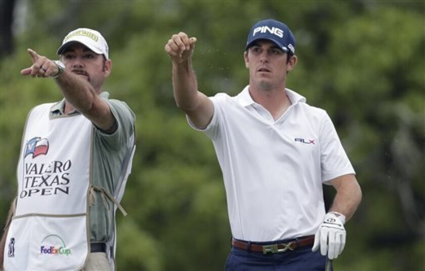 Billy Horschel, right, sprinkles grass in the air to check the wind direction on the second hole during the final round of the Texas Open golf tournament on Sunday, April 7, 2013, in San Antonio. (AP Photo/Eric Gay)