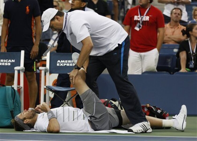 A trainer works on Mardy Fish during his match against Jo-Wilfried Tsonga of France during the U.S. Open tennis tournament in New York, Monday, Sept. 5, 2011. (AP Photo/Mel Evans)