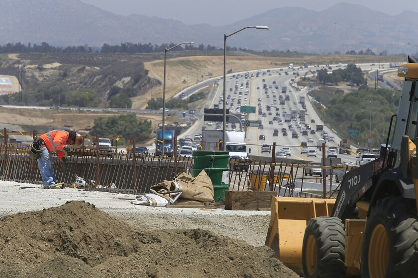 Construction crews work near Green River Road on the 91 Freeway last year. A busy section of the freeway is closed this weekend.