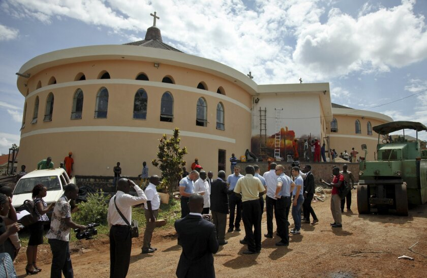 Security officials from Uganda and an advance team from the Vatican visit the Anglican Sanctuary of the Martyrs, which Pope Francis is expected to visit later in the week, at Namugongo, a suburb in the east of Kampala, in Uganda Monday, Nov. 23, 2015. More than 2 million people are expected to converge near a minor basilica in the Ugandan capital where Pope Francis will celebrate Mass on Saturday, an official with the Roman Catholic Church said Monday, even as workers put in extra hours to spruce up the shrine. (AP Photo/Stephen Wandera)