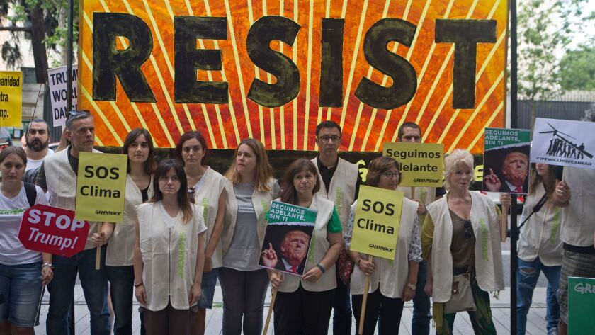 Greenpeace protesters stand in silence with banners outside the U.S. embassy in Madrid, Spain, Frida