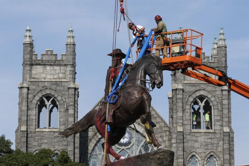 Workers attach straps to a statue of Confederate General J.E.B. Stuart.