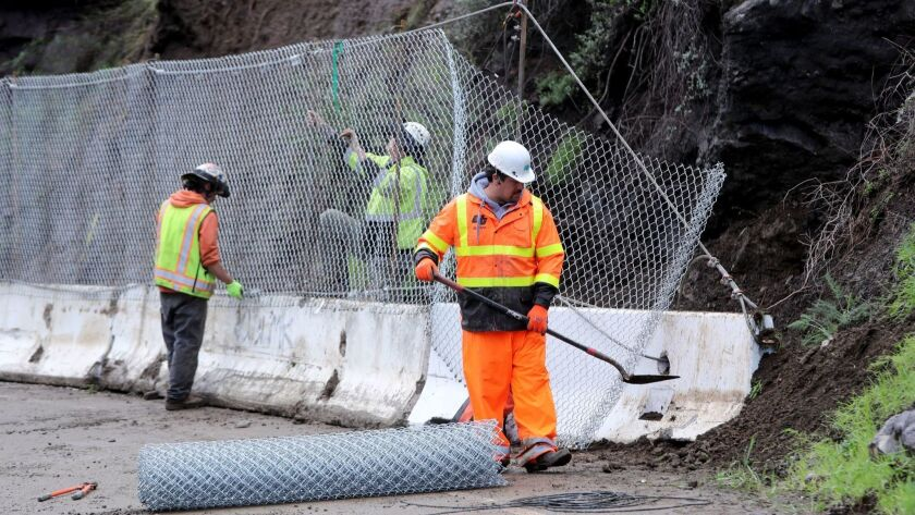 Workers erect barricades after a mudslide closed Topanga Canyon Boulevard after four days of heavy rains, USA - 04 Feb 2019